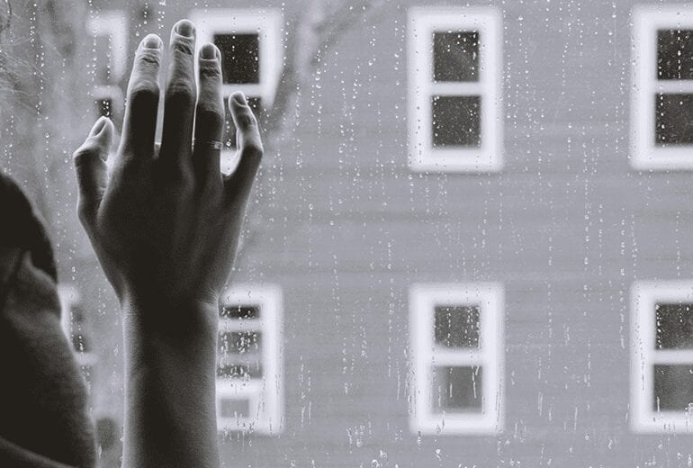 Woman's thin fraile hand pressed against a window with rain drops
