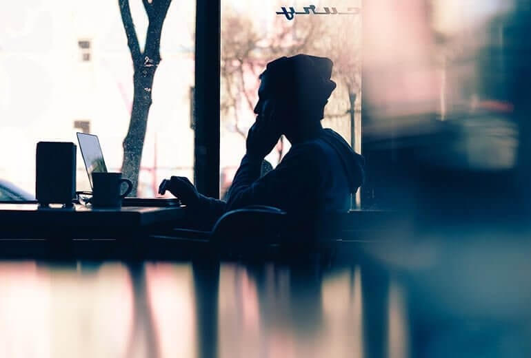 Man in coffee shop calling drug rehabs